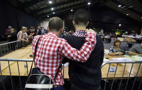 A couple watch the count at a count centre in Dublin following the vote on same-sex marriage in Ireland on May 23, 2015. Counting got under way today in Ireland's historic referendum on same-sex marriage, with thousands of people, some of whom rushed home from living abroad to vote, gathering to hear the results. AFP PHOTO /  Paul Faith