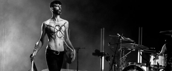 """A handout picture released by Morocco's Mawazine Festival on June 2, 2015, shows Stefan Olsdal, guitarist-bassist of the alternative British rock band Placebo, walking on stage with the number 489 written on his chest, in reference to article 489 which stipulates that homosexuality is punishable in Morocco by up to three years in jail, during the 14th edition of the music festival in Rabat. Placebo used their appearance at a Moroccan music festival to protest the kingdom's gay rights record in a performance that saw a band member play a rainbow-coloured guitar. AFP PHOTO / HO / SIFE EL AMINE == RESTRICTED TO EDITORIAL USE - MANDATORY CREDIT """"AFP PHOTO / HO / SIFE EL AMINE"""" - NO MARKETING NO ADVERTISING CAMPAIGNS - DISTRIBUTED AS A SERVICE TO CLIENTS =="""
