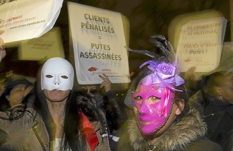 """A prostitute holds a placard reading """"clients penalised- prostitutes killed"""" as others wear masks during a demonstration of sex workers on December 4, 2013 in Paris, after French lawmakers approved today a controversial bill that will make the clients of prostitutes liable for fines starting at 1,500 euros ($2,000). AFP PHOTO / JOEL SAGET"""